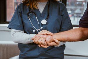A nurse holding a patients hand